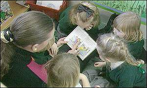 A teacher reads nursery rhymes in a nursery class