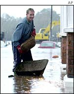 A man adds more sandbags to the steps of his home during floods in Upton upon Severn, western England, in November 2000