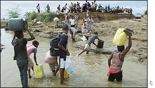 Villagers cross a river close to a collapsed bridge in Mozambique
