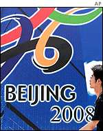 Man walks past Beijing Olympic bid logo