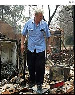 A man looks at the remains of his burnt house