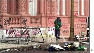A worker cleans debris outside Buenos Aires Government House, daubed with graffiti