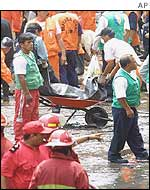 Emergency workers remove bodies from the wreckage