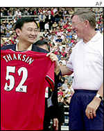 Manchester United manager Alex Ferguson, right,  gives his team's shirt to Thailand Prime Minister Thaksin Shinawatra at a friendly match in July 2001 between Thailand and Manchester United