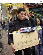 Policeman removes box of fireworks from scene in Lima