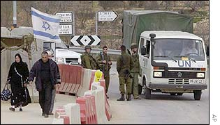 Palestinians pass an Israeli roadblock near Behtlehem