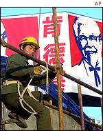 A Chinese worker in front of a KFC sign