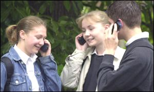 Three girls talk on mobile phones