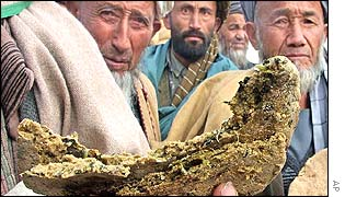 Men hold up bread made of grass in the town of Zari, northern Afghanistan