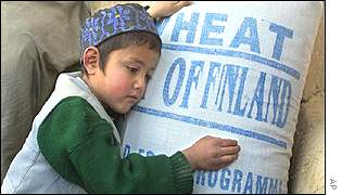 An Afghan boy hugs a bag of wheat from Finland, delivered by the WFP
