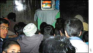 Afghanis crowd round a TV set to watch a video