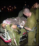 Israeli troops tend to injured comrade