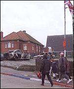 Residents walk past a burnt out car on the Ardoyne Road