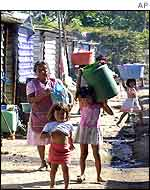 Women carry water in one of the temporary camps set up after the disaster