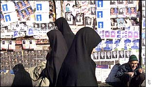 Women walk in front of posters for MP elections in Tehran