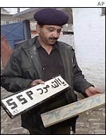 A policeman removes the sign board of Sipah-e-Sahaba in Quetta
