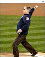 Mr Bush throws  ceremonial first pitch at baseball match at New York's Yankee Stadium, Oct 2001