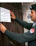 A policeman posts the order at the office of Jaish-e-Mohammad in Multan