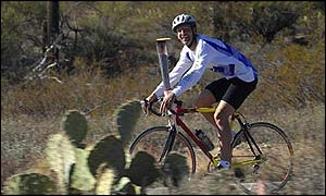 13 Jan 2002: Torchbearer Dwight Nelson carries the Olympic Flame through the desert on his bicycle during the 2002 Salt Lake Olympic Torch Relay in Tucson, Arizona.