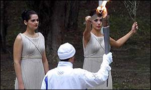 19 Nov  2001: The High Priestess, Thalia Prokopiou lights the torch of the first torch bearer Lefteris Fafalis of Greece in the Pierre de Coubertin Grove in Olympia, Greece