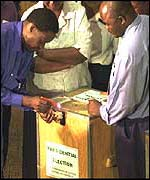 Government officials demonstrate a sample polling station
