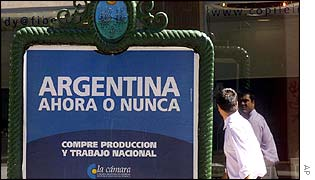A man walks near a sign in Buenos Aires that reads: Argentina, now or never. Buy national products and labour