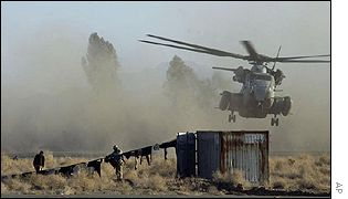 US troops hang out their laundry as a helicopter lands at the Kandahar base