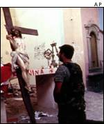 Soldier praying before crucifix   AP