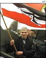A right-wing demonstrator holds a German Reich war flag flags during a demonstration in Berlin