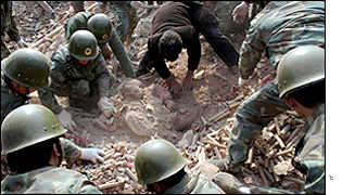 Rescue workers pull a survivor from the rubble of a factory explosion, January 2002