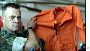 US soldier displays jumpsuit as worn by al-Qaeda detainees at Guantanamo