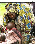 A woman carrying bundles and baby as she flees Goma