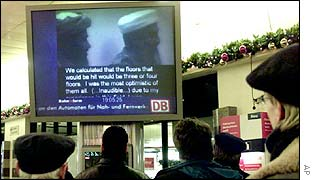 Passengers at Berlin Zoo station watch a video of Osama Bin Laden