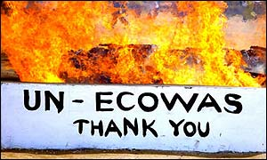 A sign in front of burning rebel weapons thanking the UN and the Economic Community of West African States