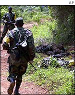 Colombian soldier passes bodies of dead comrades at site of ambush at Pichinde, near Cali