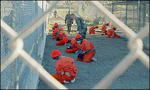 Prisoners kneeling in front of guards at the Guantanamo bay camp
