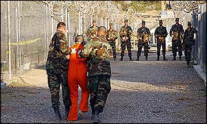 US soldiers walks along with shackled prisoner