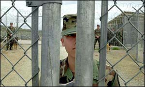 A soldier stands at the gates to the camp at Guantanamo Bay