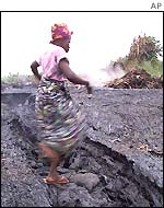 A Congolese woman jumps across lava rock in the western town of Monigi, Congo near Goma