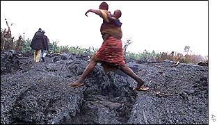 A Goma woman carrying her child jumps the lava