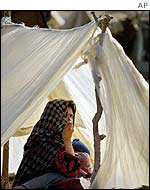 Woman sits in tent at displaced people's camp