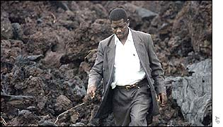 Vulcanologist Dieudonne Wafula walks past lava rock at Goma airport