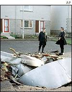 Police guard a piece of debris