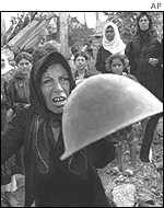 A Palestinian woman holds a helmet at a memorial service