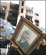 A worker carries of picture of Yasser Arafat from the PBC building