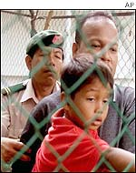 A security guard tries to stop Habib Peter (r) an his nephew from speaking to the media from across the fence