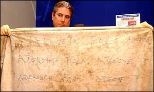 Exhibits Officer DC Mark Ham holds up a sheet covered in mud stains and with a name written on it three times