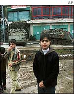 Palestinian children with Israeli armoured vehicles in the background