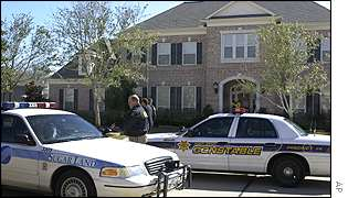 Police cars outside the home of former Enron vice chairman J. Clifford Baxter