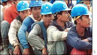 Indonesian labourers wait on ground outside a police station